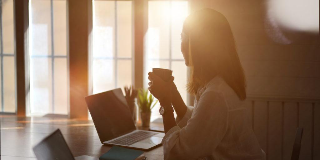 A kép az online végzett tartalommarketing és tartalomgyártás tanácsadás előnyeit szimbolizálja - a hölgy laptopja előtt ülve kényelmesen kávét szürcsöl.
