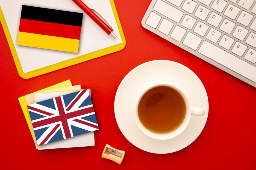 A képen egy csésze kávé, valamint egy német és egy angol zászló látható, az angol magyar és a német magyar fordítást szimbolizálva.