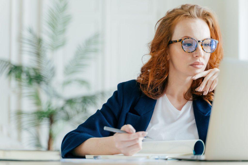 A képen egy nő gondolkodik a számítógépe előtt, a szövegírás nehézségeit szimbolizálva.